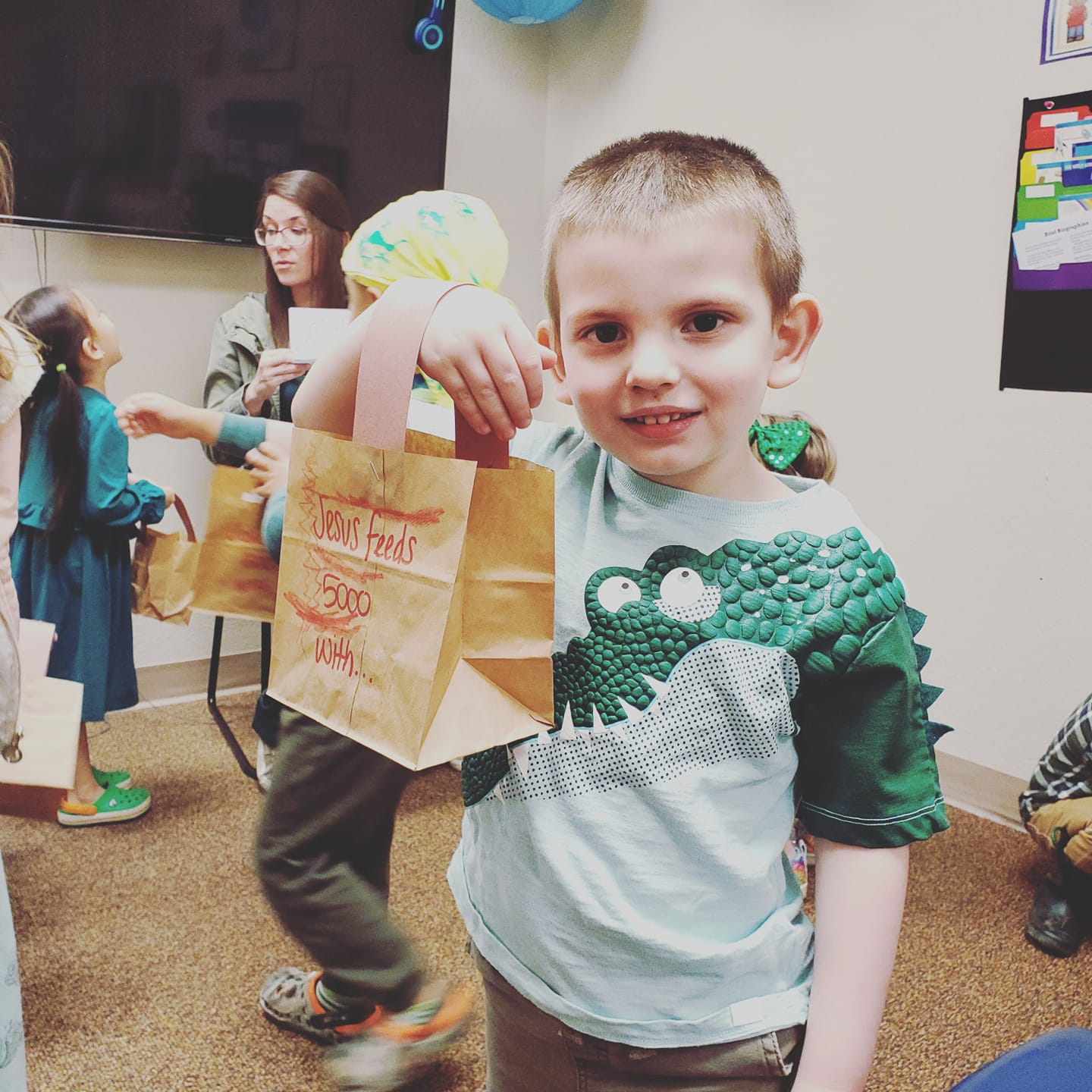 A child holding up a bag in a children's class